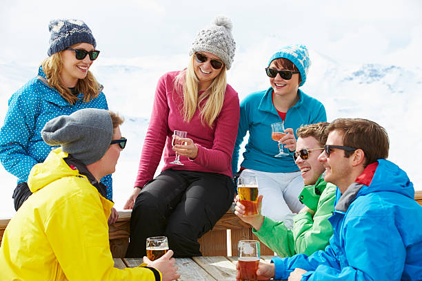 Friends enjoying drinks at a ski resort Group Of Friends Enjoying Drink In Bar At Ski Resort Chatting And Laughing. apres ski stock pictures, royalty-free photos & images