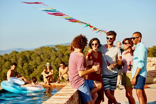 Friends enjoying drinks at poolside