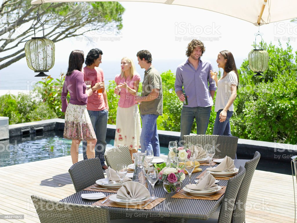 Friends Enjoying Drinks Near Fine Table Setting stock photo