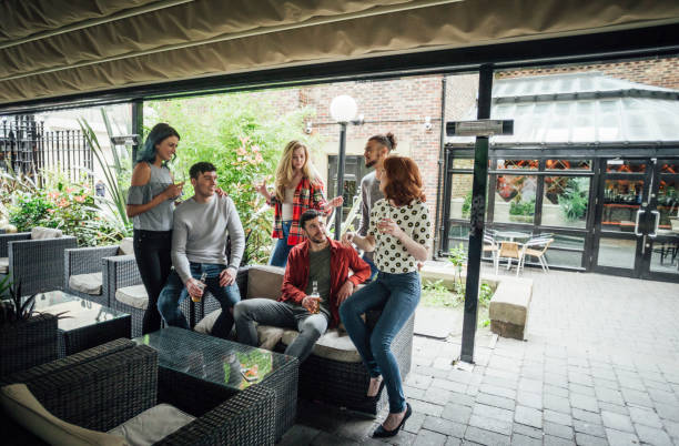 Friends Enjoying Drinks Together Group of friends are enjoying drinks as they chat in a bar courtyard. courtyard stock pictures, royalty-free photos & images