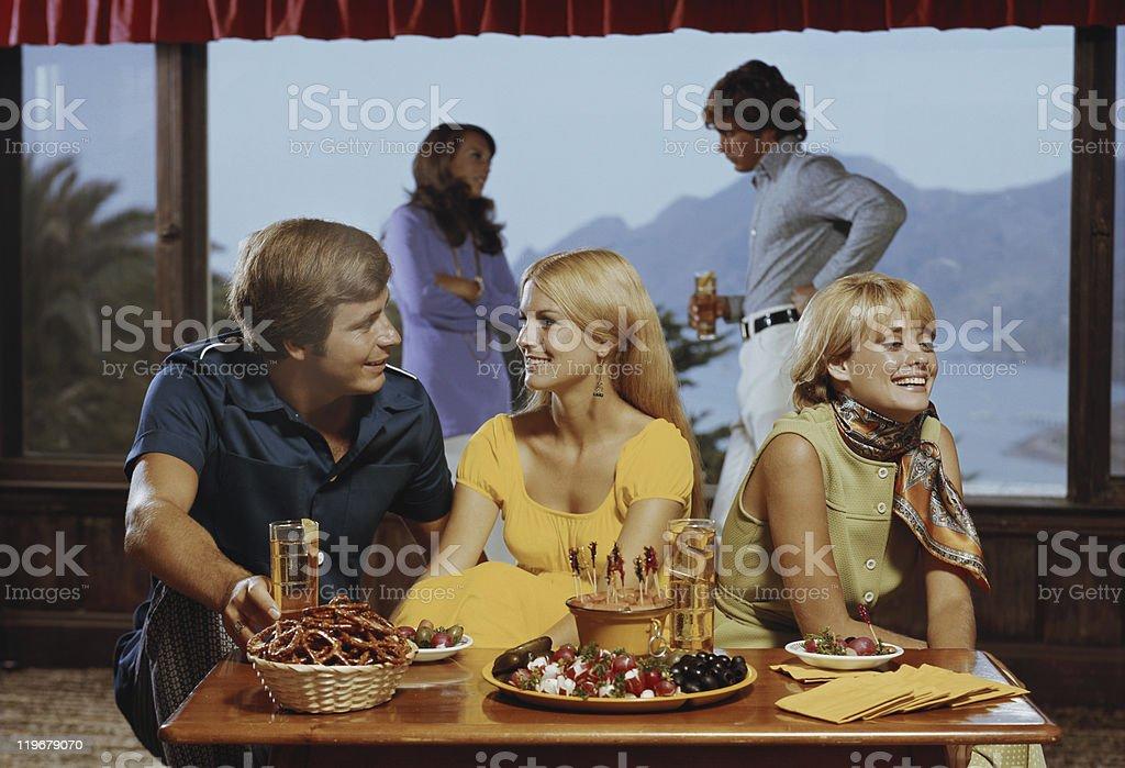 Friends enjoying food in living room stock photo
