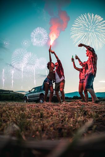 Friends enjoying holidays celebrating outdoors with fireworks