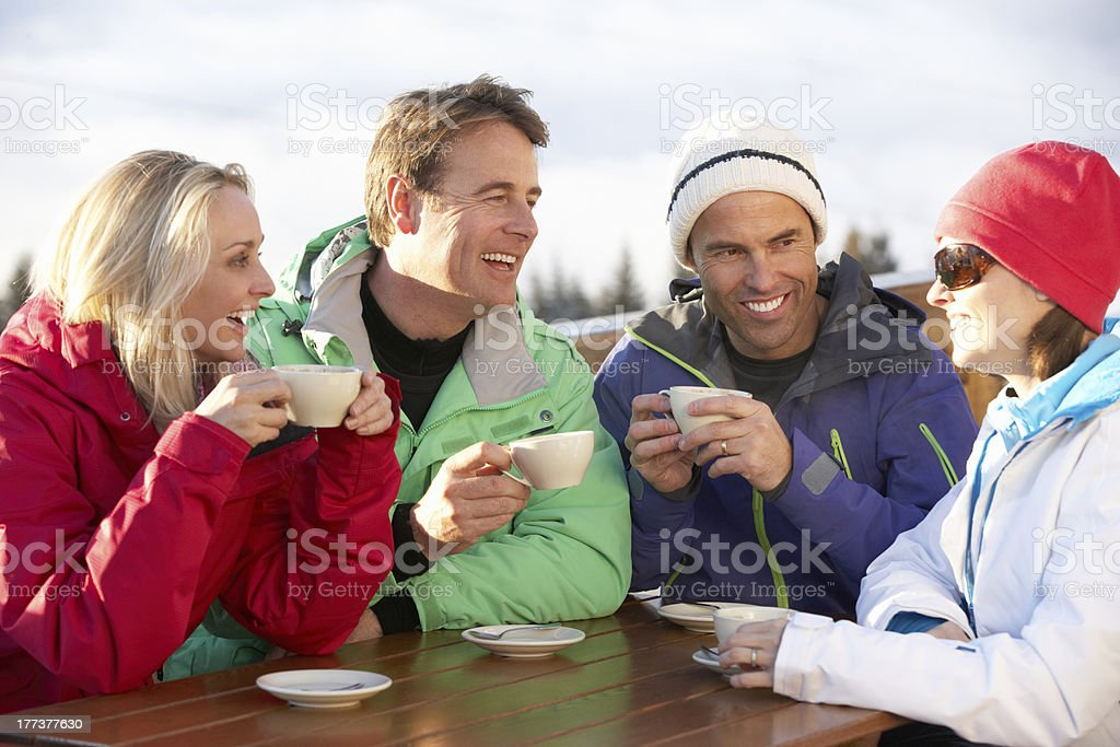 Friends Enjoying Hot Drink In Café At Ski Resort stock photo