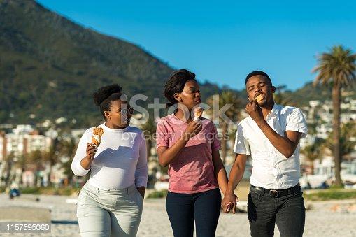 istock Friends enjoying ice creams while walking at beach 1157595060
