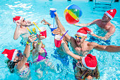 Group of friends swimming and drinking in swimming pool during pool party, wearing Santa hat and holding drinks.
