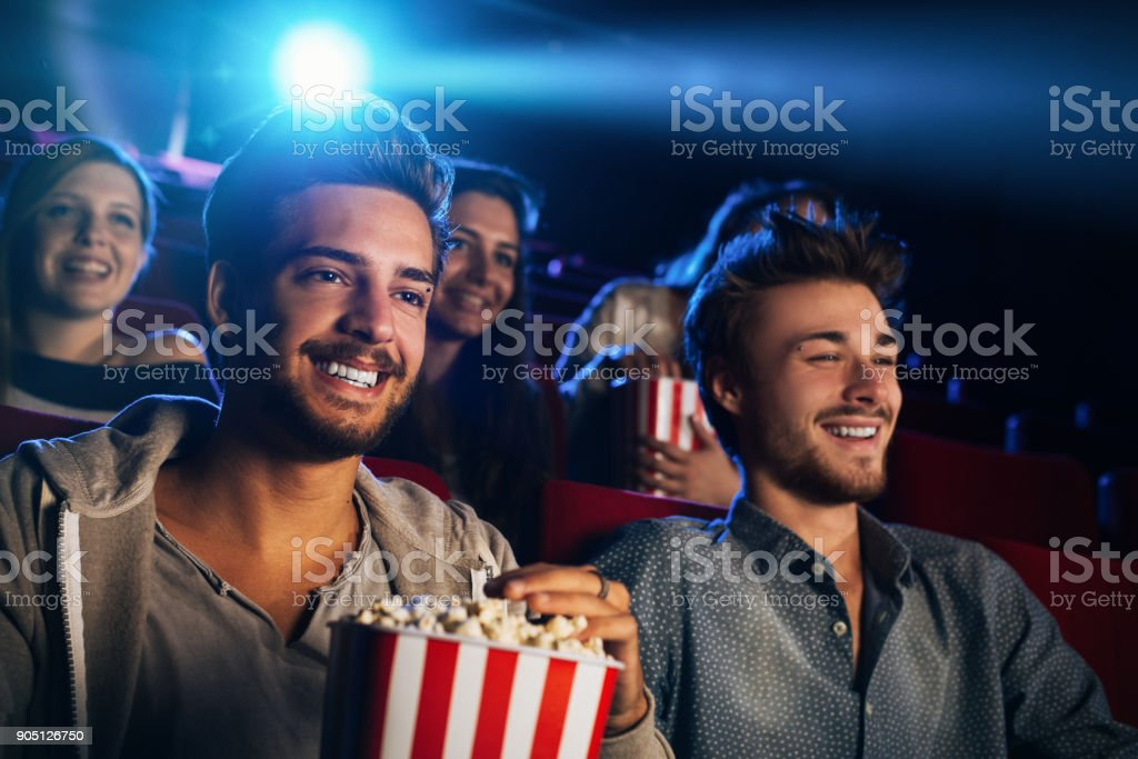 Friends enjoying in the movie theater stock photo