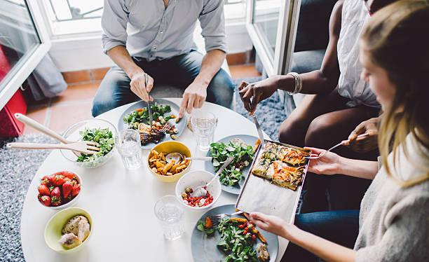 friends enjoying lunch at home - porsiyon ölçüsü stok fotoğraflar ve resimler