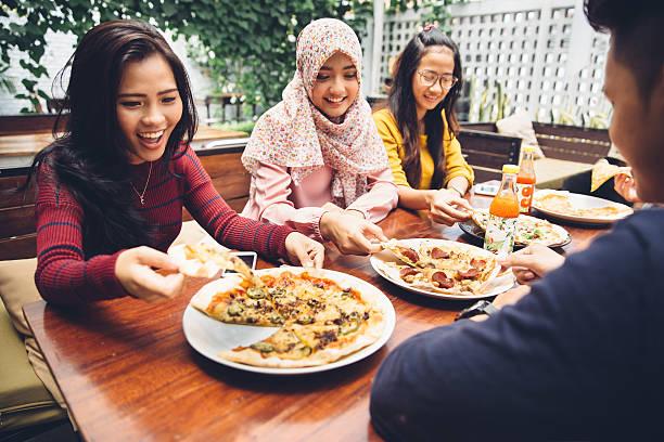 Friends Enjoying Meal In Outdoor Restaurant - foto de acervo