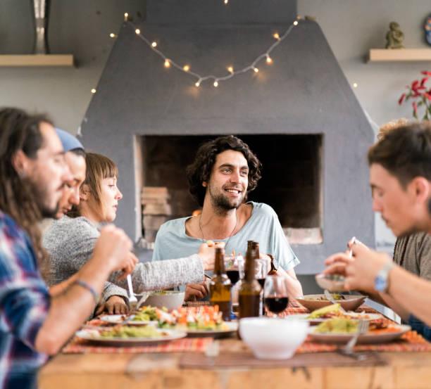 freunde, die mahlzeit am tisch sitzend genießen - bier gesund stock-fotos und bilder