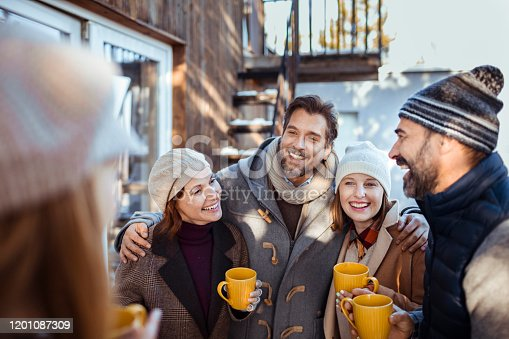 Close up of a group of friends having Mulled Wine while enjoying time together on the porch during winter