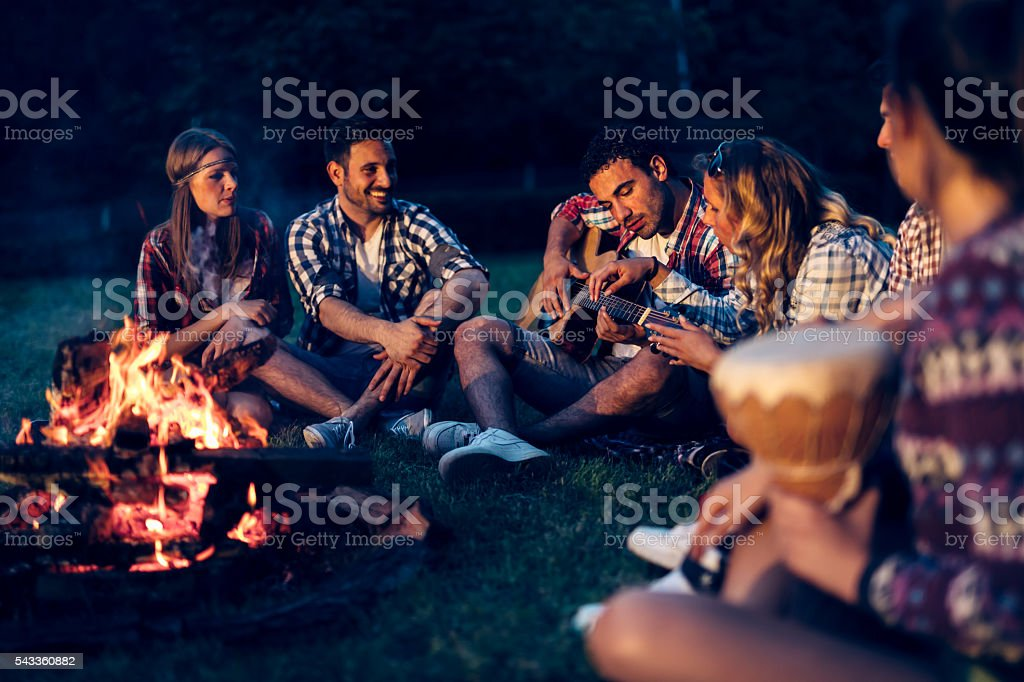 Friends enjoying music near campfire stock photo