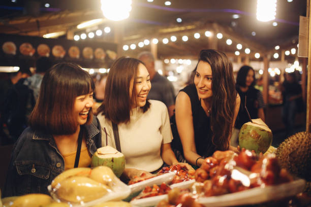 Friends enjoying night time food markets in Bangkok Young girl friends enjoying late night food and shopping in one of the Bangkok's street markets. night market stock pictures, royalty-free photos & images