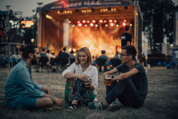 Friends enjoying on concert Group of people, sitting on grass and drinking beer on a concert, summer festival. traditional festival stock pictures, royalty-free photos & images