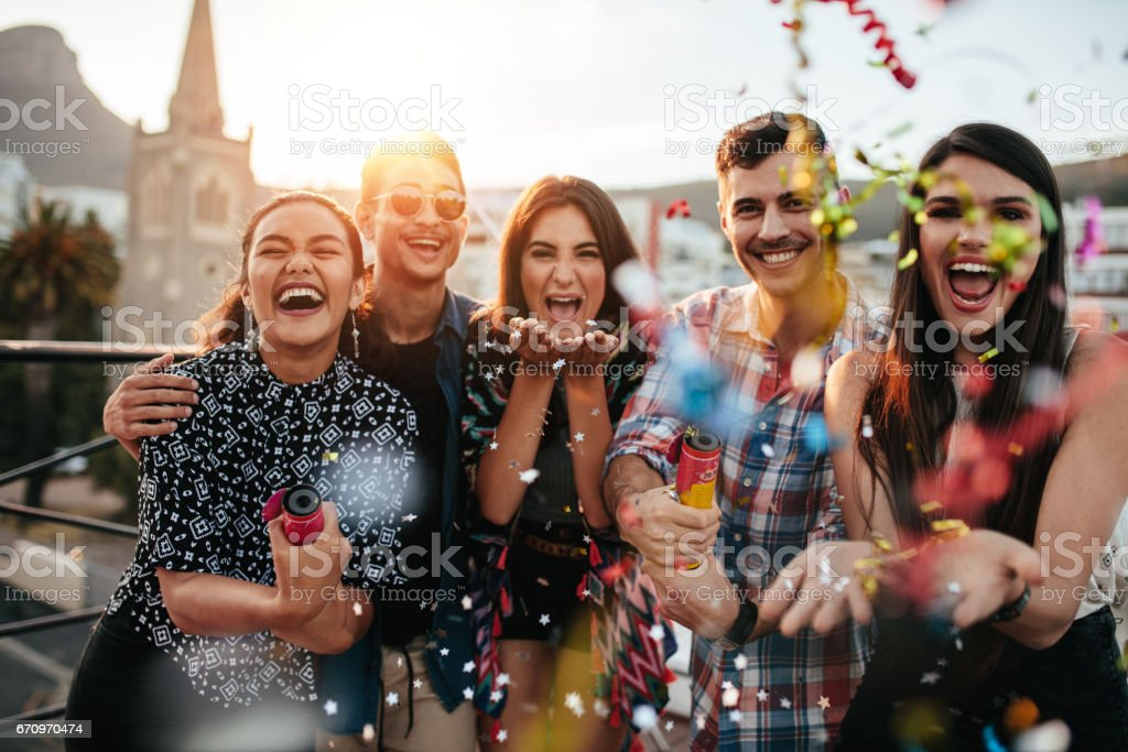 Friends enjoying party and  throwing confetti stock photo