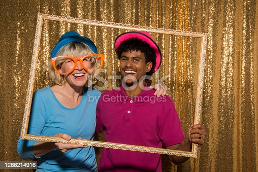 Portrait of cheerful friends with photo frame prop enjoying party.