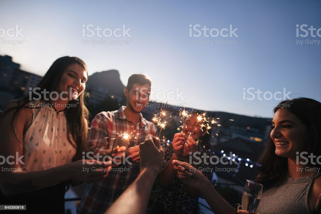 Friends enjoying rooftop party with sparklers stock photo