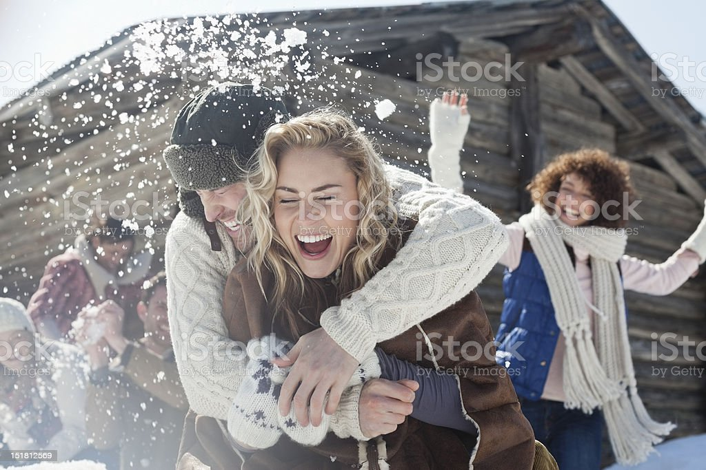 Friends enjoying snowball fight stock photo