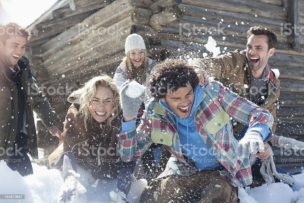 Friends enjoying snowball fight stock photo