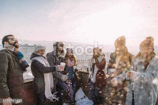 Smiling group of friends drinking hot drinks outdoors, on the sunny winter afternoon. They are at the rooftop terrace that overlooks the city.