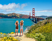 Girls enjoying time together on vacation  trip.  Girls looking at beautiful view of Golden Gate Bridge, over Pacific Ocean. San Francisco, California, USA
