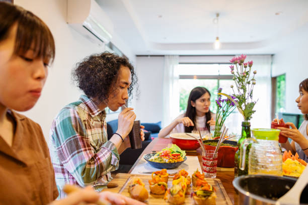 freunde genießen vegetarisches essen zu hause party - jamaikanische party stock-fotos und bilder