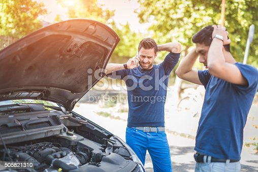istock Friends examining broken down car on sunny day 505821310