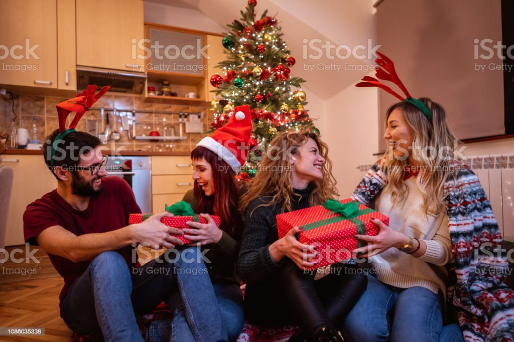 Friends Exchanging Christmas Presents Stock Photo Download Image