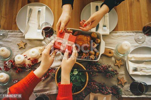 1059144984 istock photo Friends exchanging gifts at the Christmas dinner 1184823715