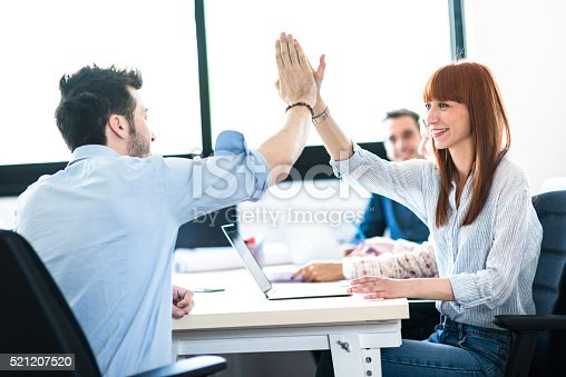 istock friends exchanging the highfive in the office 521207520