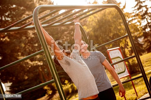 Multi-ethnic male friends exercising in the outdoor gym.