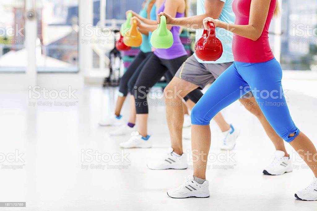 Friends Exercising With Kettle Bells In Health Club royalty-free stock photo