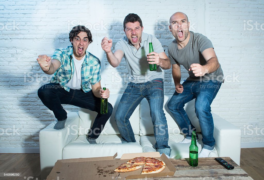 friends fanatic football fans watching game on television celebrating goal stock photo