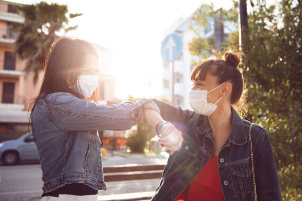 Friends finally meet again in the streets, holding hand wearing protective gloves stock photo