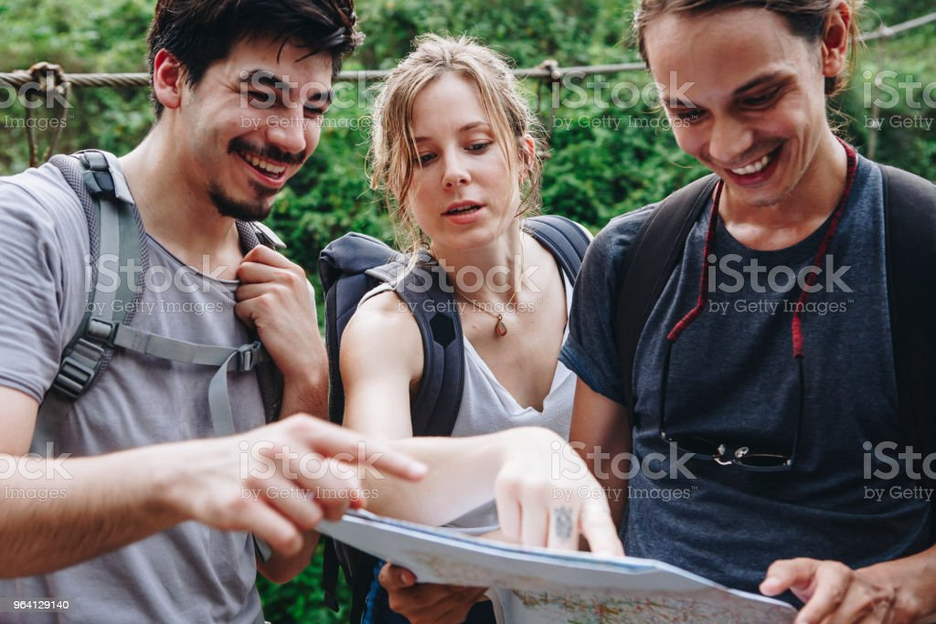 Friends finding their way with a map stock photo