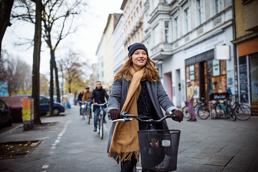 Young woman cycling on road by buildings. Male and female friends following her in city. They are traveling during winter.