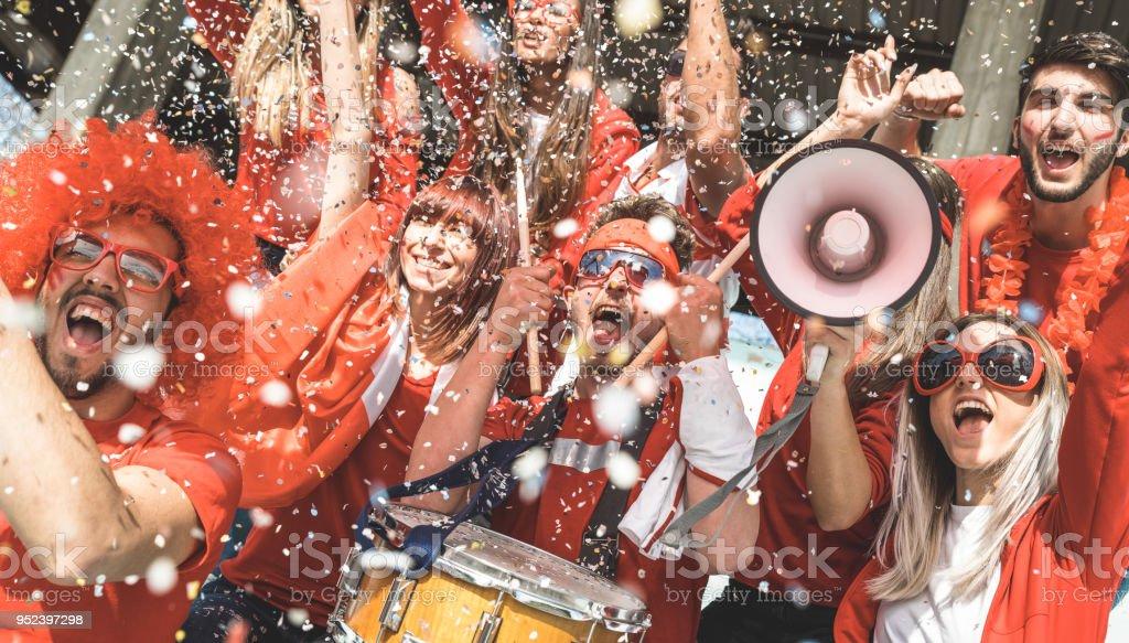 Amigos partidario los aficionados al fútbol que anima con el fútbol viendo confeti coinciden con eventos en el estadio - grupo de jóvenes con camisetas rojas que excitó la diversión en concepto de Campeonato del mundo de deporte foto de stock libre de derechos