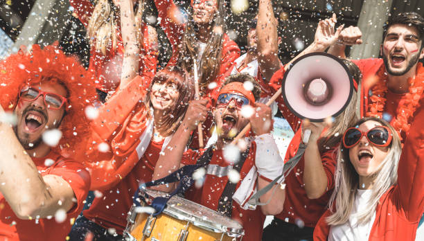 Friends football supporter fans cheering with confetti watching soccer match event at stadium - Young people group with red t-shirts having excited fun on sport world championship concept stock photo