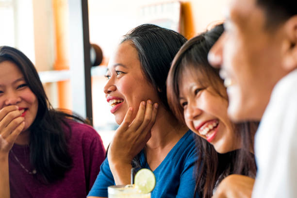 Friends forever Three young girls and one young man sitting in a caffe and having fun while smiling. There is a drink on the table. Shot made in Mataram, Lombok, Indonesia in July 2017. indonesian ethnicity stock pictures, royalty-free photos & images