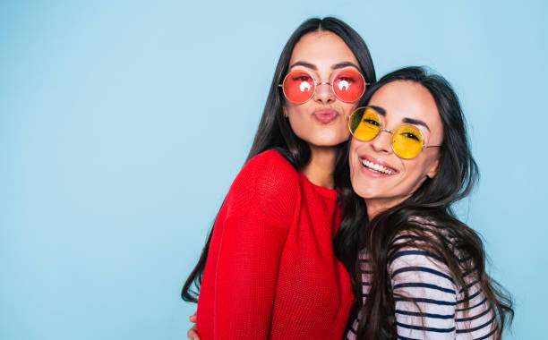 friends forever. two cute lovely girl friends in sunglasses posing with smile on blue background - amici foto e immagini stock