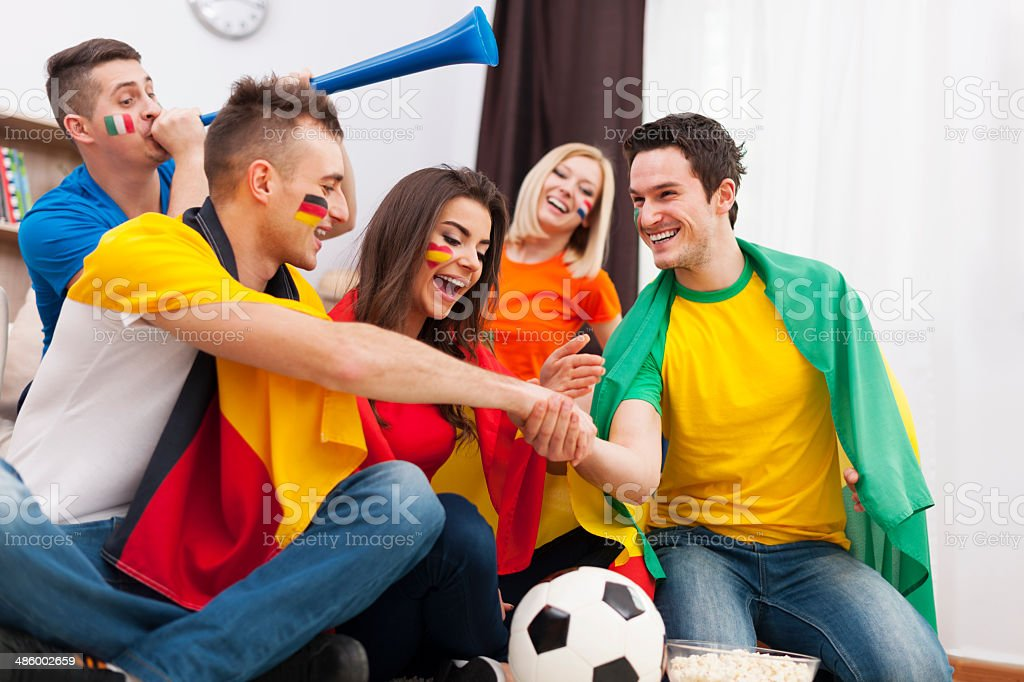 Friends from different country supporting football team stock photo