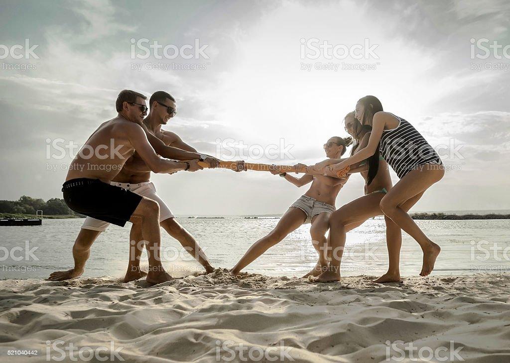 Friends funny on the beach under sunset sunlight. stock photo