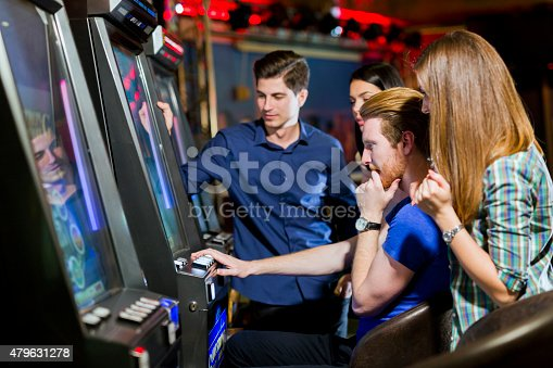 istock Friends gambling in a casino playing slot and various machines 479631278