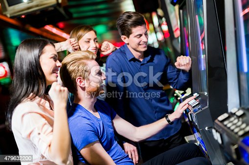 istock Friends gambling in a casino playing slot and various machines 479632200