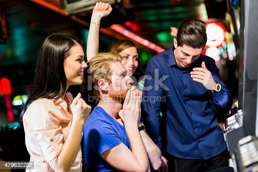 istock Friends gambling in a casino playing slot and various machines 479632202