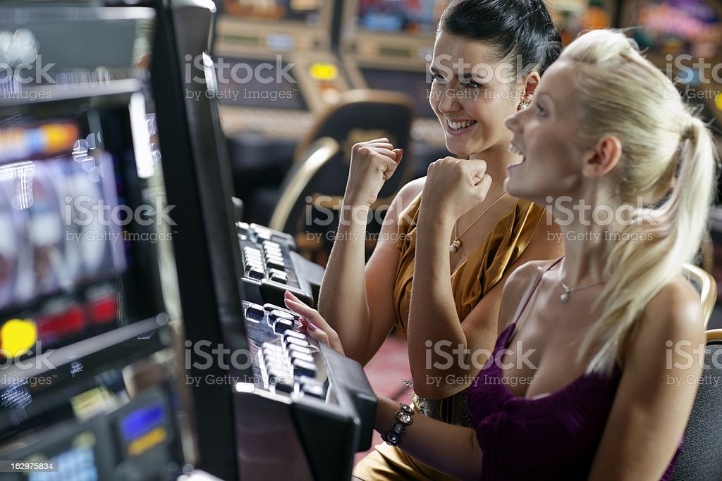 friends gambling in the casino on slot machines stock photo