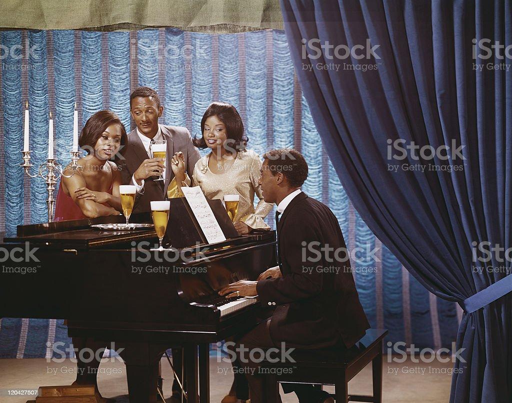 Friends gathered around man playing piano stock photo