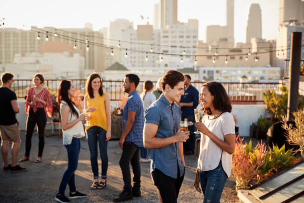 Friends Gathered On Rooftop Terrace For Party With City Skyline In Background stock photo