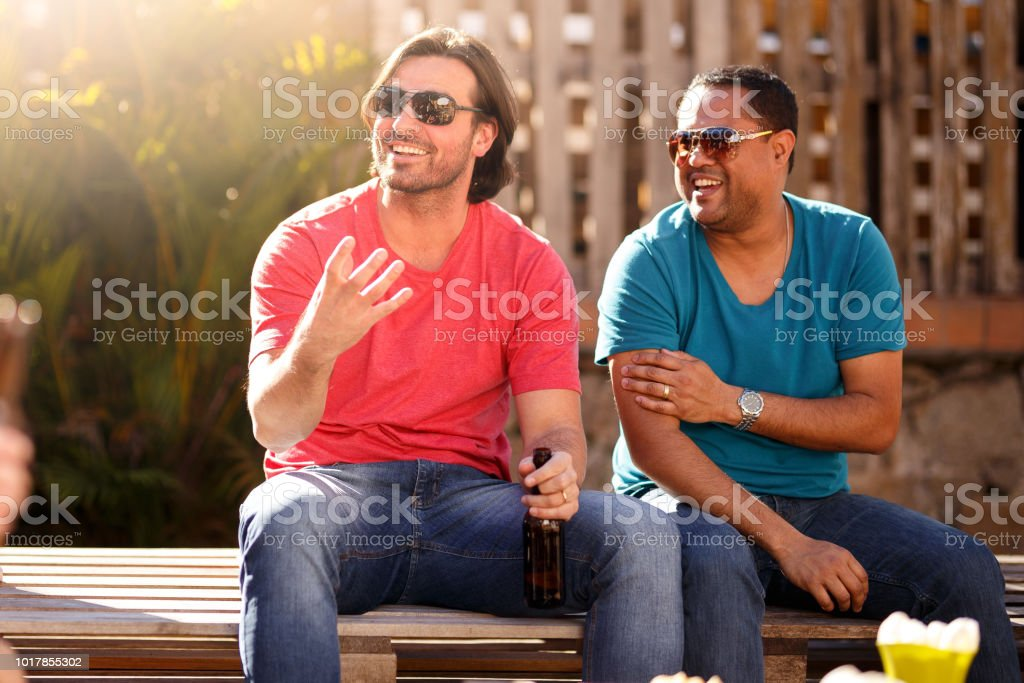 Two friends having fun gathering in a rooftop for food and drink.