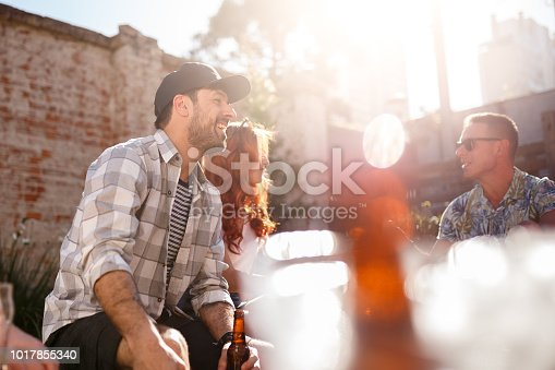 A group of friends having fun gathering in a rooftop for food and drink.