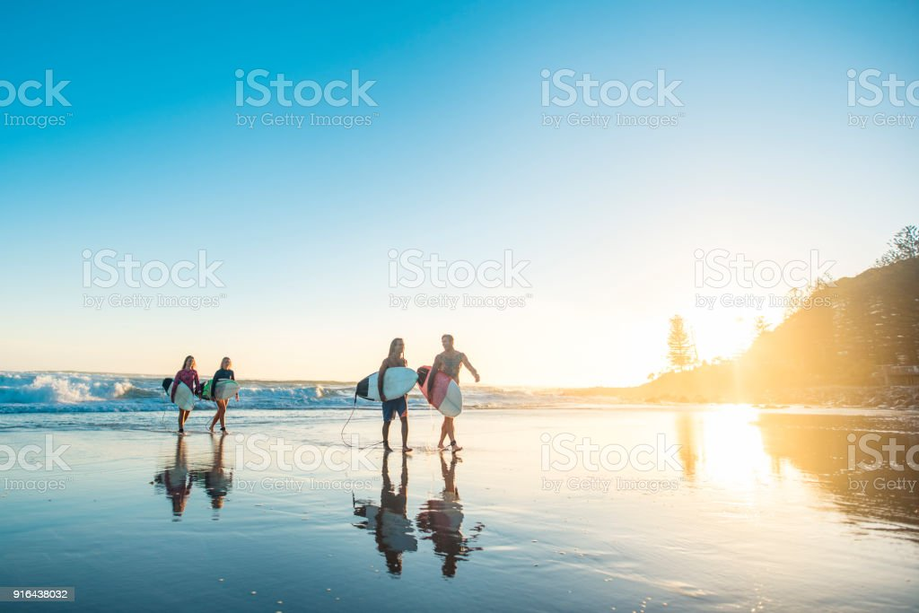 Friends getting out of the water at sunset after surfing stock photo